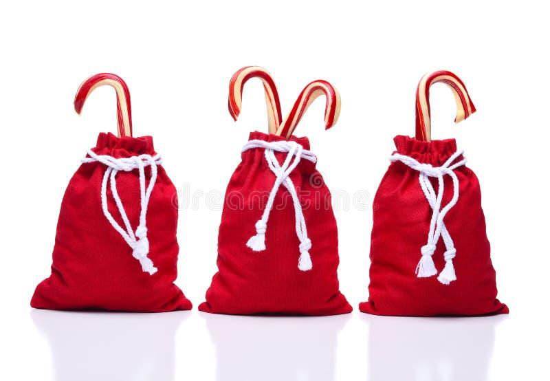 Drei rote Santa Toy Bags mit einer Schnur des abgehobenen Betrages, welche die Taschen gürtet, schlossen stockfotografie