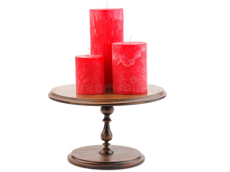 Drei rote Wachskerzen unterschiedlich im Durchmesser, auf einem Kerzenständer, lokalisiert auf einem weißen Hintergrund stockbilder