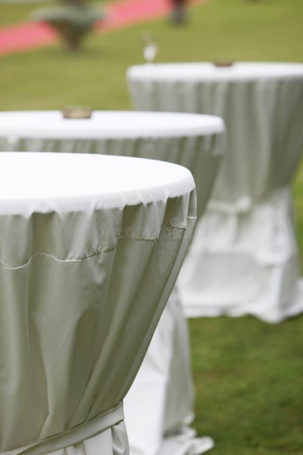 Drei Rundtische eingewickelt in der weißen Tabellenkleidung stockbilder