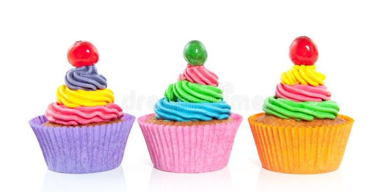 Drei süße bunte kleine Kuchen lizenzfreies stockbild
