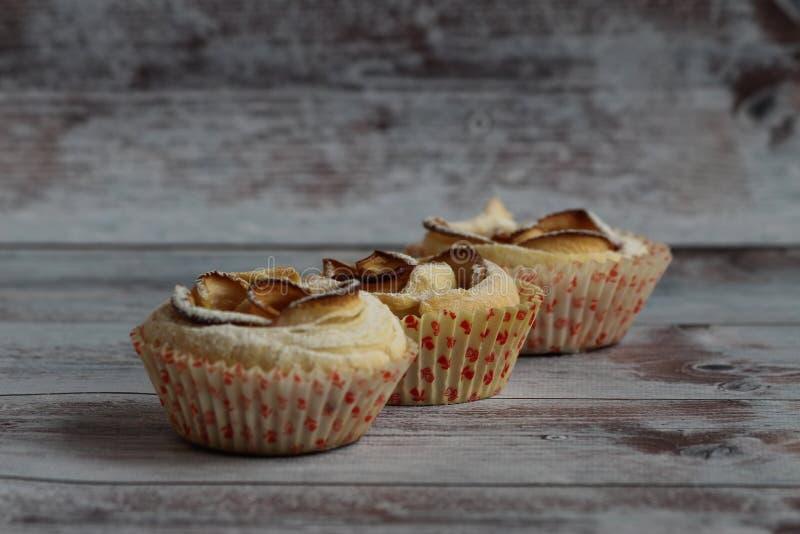 drei süße Kuchen im Puderzucker stehen auf einem hellen Hintergrund stockfotografie