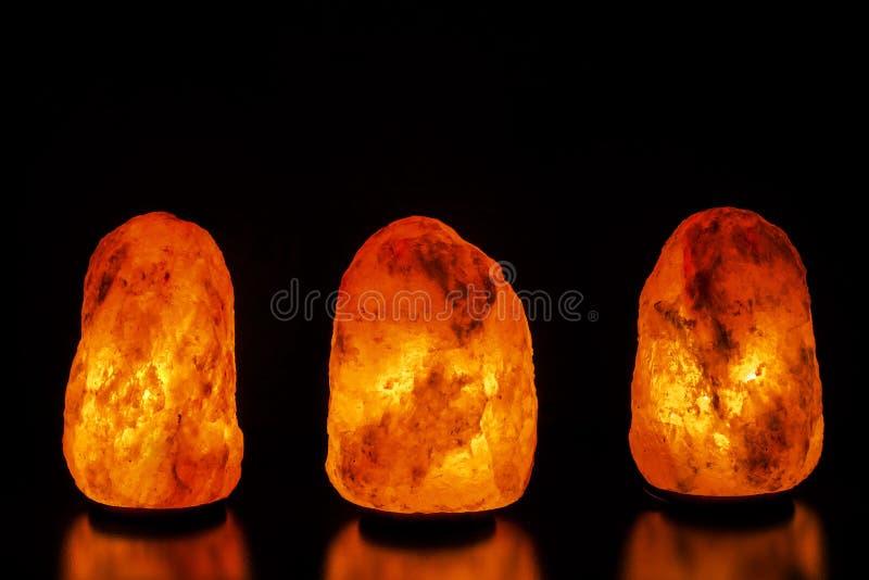 Drei Salzlampen auf schwarzem Hintergrund stockbilder