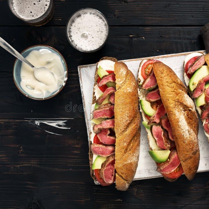 Drei Sandwiche mit dem Rindfleisch gegrillt und Bier auf hölzernem Brett stockbilder
