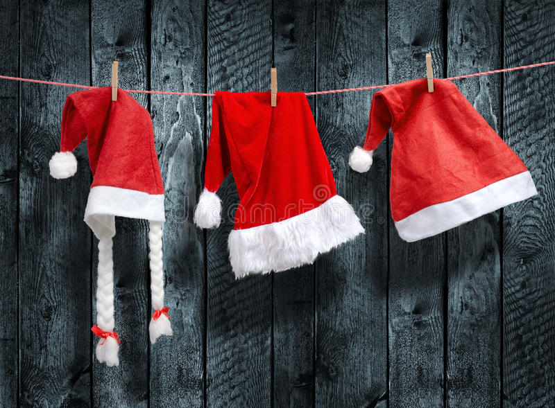 Drei Santa Claus Hut, der an einer Wäscheleine hängt stockbilder