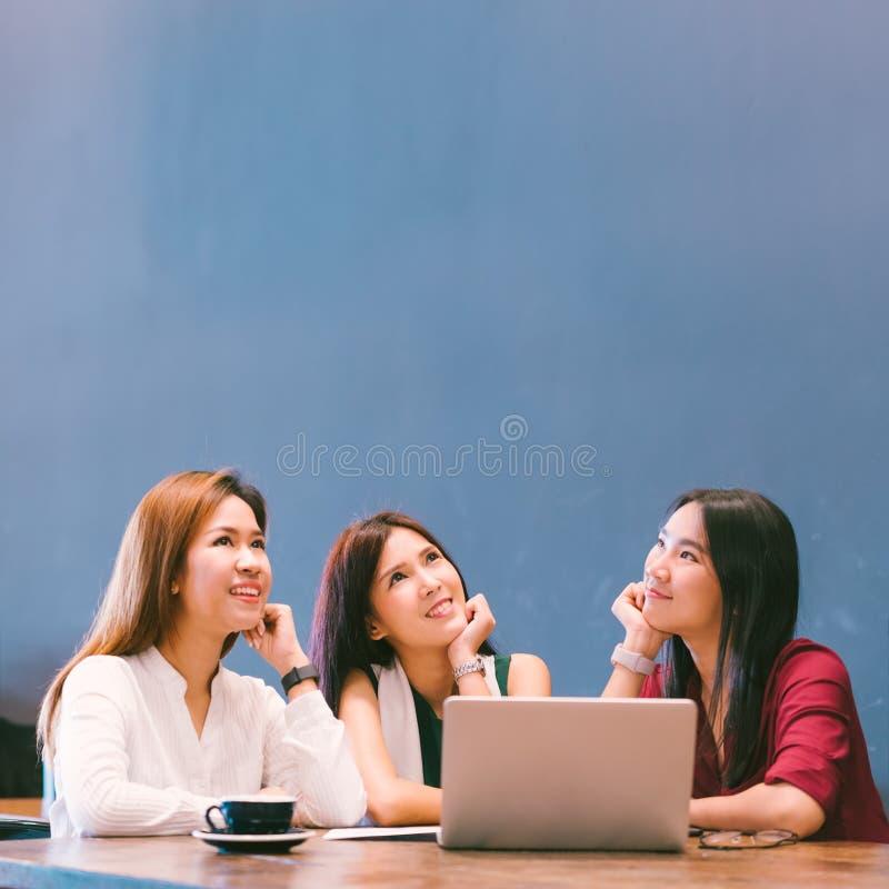Drei schöne asiatische Mädchen, die aufwärts schauen, um Raum beim Arbeiten zu kopieren am Café stockfotografie