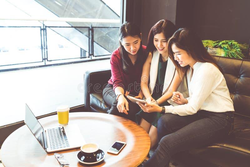 Drei schöne asiatische Mädchen, die den Smartphone und Laptop, plaudernd auf Sofa am Café verwenden stockfotos