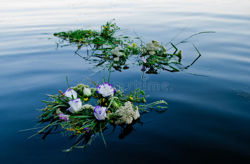 Drei schöne Blumensträuße ein Kranz von den Blumen, die entlang das Flussruhewasser von Ivan Kupala schwimmen lizenzfreies stockbild