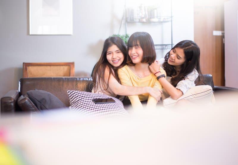 Drei schöne junge asiatische Freundinnen, die zusammen lächeln und lachen sprechen stockfotos