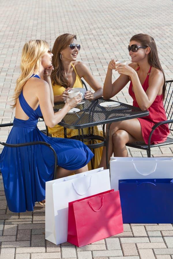 Drei schöne junge Frauen, die Kaffee trinken stockfotografie