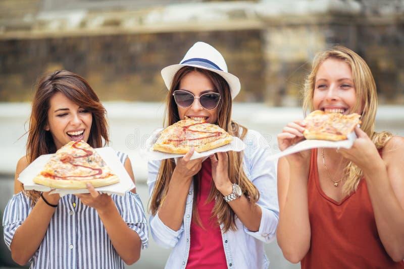 Drei schöne junge Frauen, die Pizza nach dem Einkauf essen lizenzfreie stockfotografie
