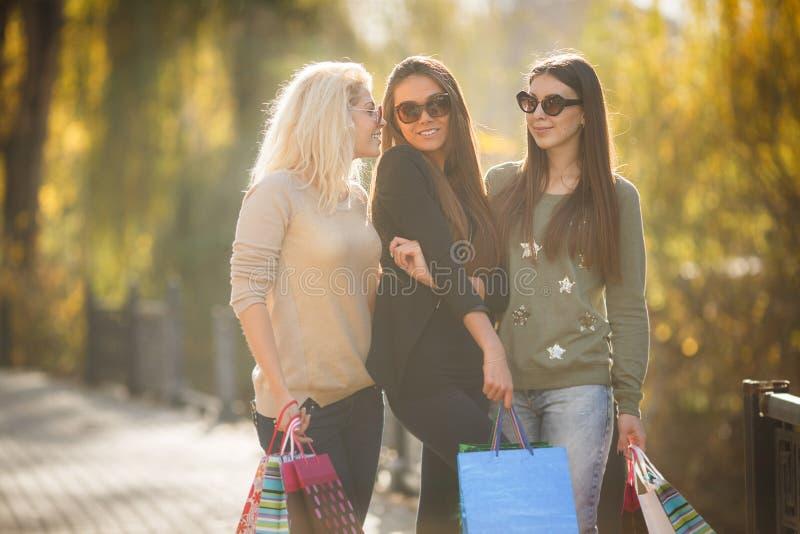 Drei schöne junge Frauen mit Einkaufstaschen stockfotos