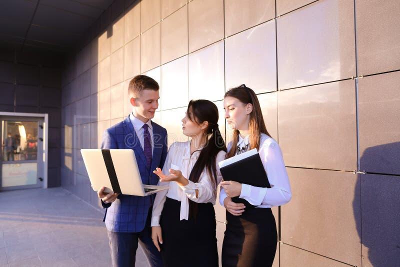 Drei schöne junge Leute, Studenten, zwei Mädchen und Junge halten i lizenzfreie stockfotografie