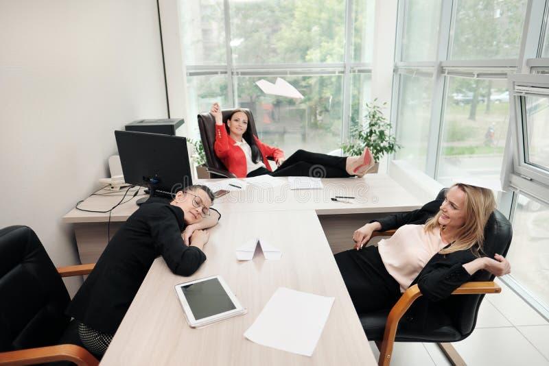 Drei schöne junge Mädchen in den Anzügen sitzen am Schreibtisch Erm?det worden von der Arbeit Wurfspapierflugzeuge und stockfotos