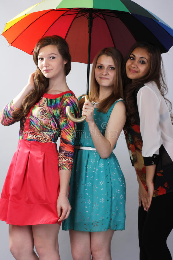 Drei schöne Mädchen, unter einem Regenschirm stockfoto