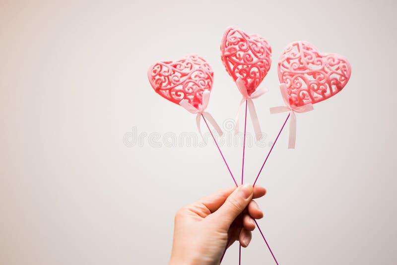Drei schöne rosa Herzen auf der Hand der Frau auf weißem Hintergrund Valentinsgruß `s Tag Symbol der Liebe stockbilder