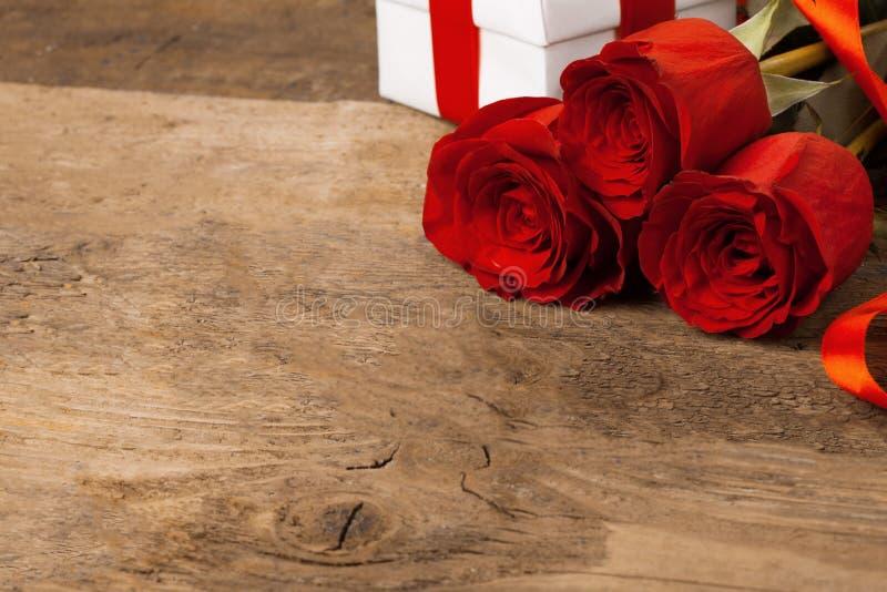Drei schöne rote Rosen liegen auf einer Holzoberfläche stockfotos
