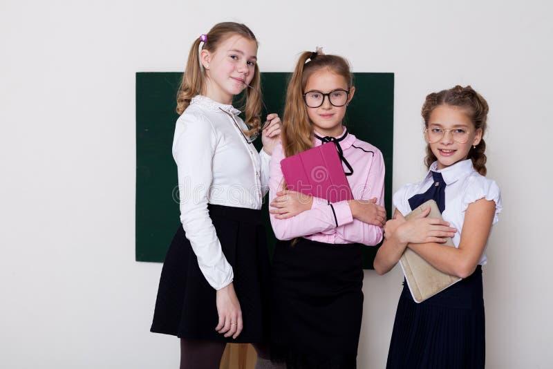 Drei Schülermädchen, die in der Klasse an der Schulverwaltung stehen stockfoto
