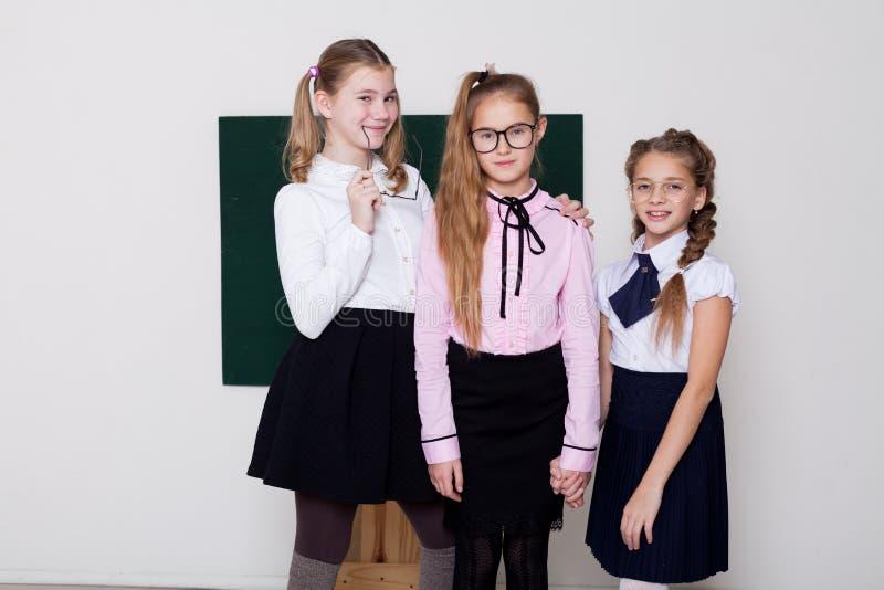 Drei Schülermädchen, die in der Klasse an der Schulverwaltung stehen stockfotos