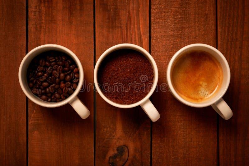 Drei Schalen Espresso, frisch gemahlener Kaffee und Kaffeebohnen auf einem Holztisch stockfoto