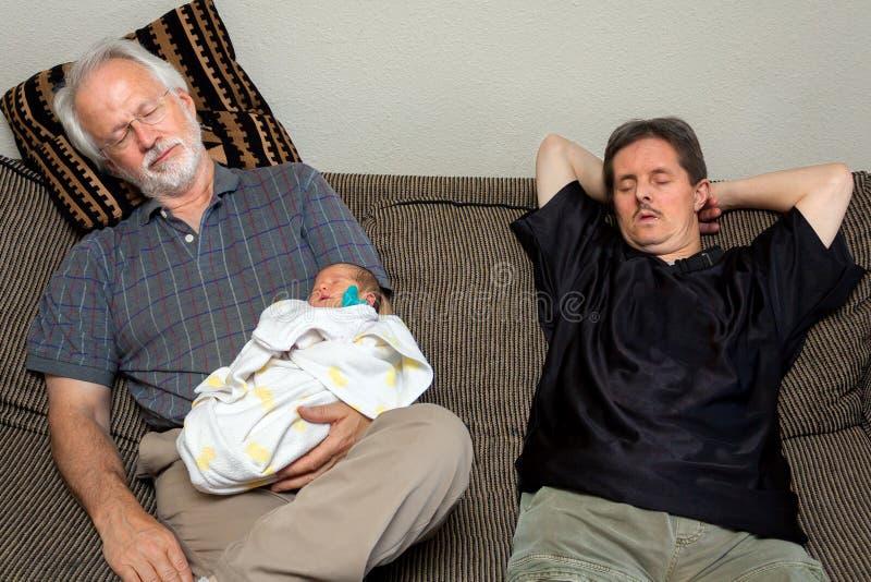 Drei schlafend auf einem Couch-neugeborenen Baby-Großvater und einem Mann mit tun stockfoto