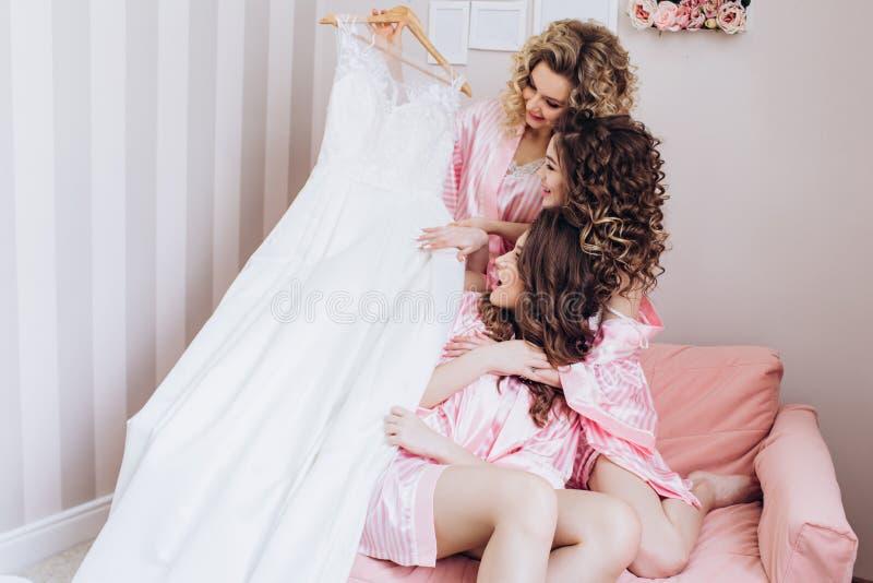 Drei schlank, junge, schöne Mädchen in den rosa Pyjamas betrachten ein Heiratskleid stockfotos