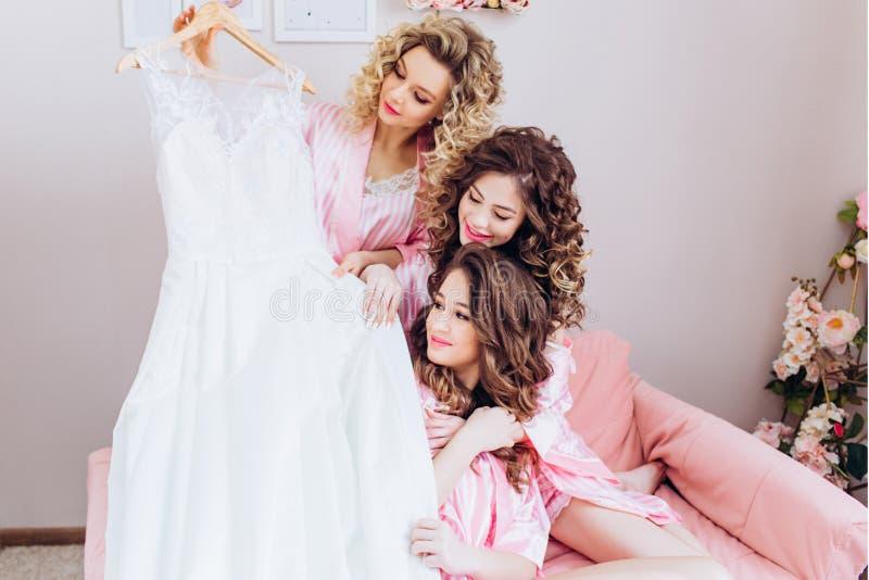 Drei schlank, junge, sch?ne M?dchen in den rosa Pyjamas betrachten ein Heiratskleid lizenzfreie stockfotografie