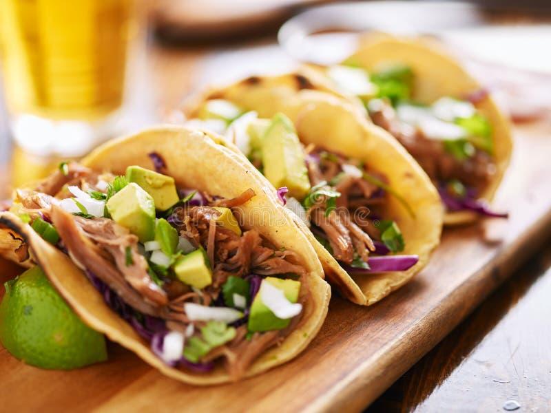 Drei Schweinefleisch carnitas Straßentacos in der gelben Maistortilla mit Avocado, Zwiebel, Koriander und Kohl lizenzfreie stockfotografie
