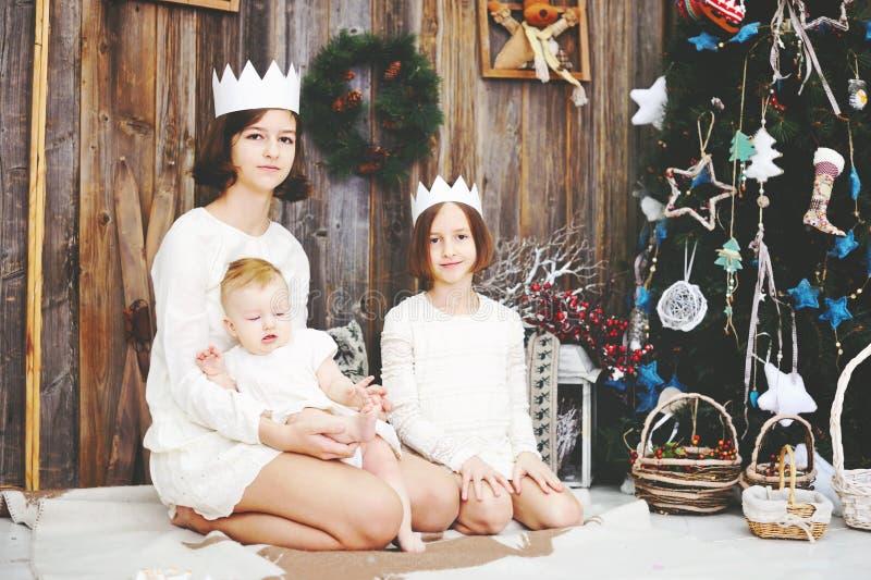 Drei Schwestern, die vor Weihnachtsbaum aufwerfen lizenzfreies stockfoto
