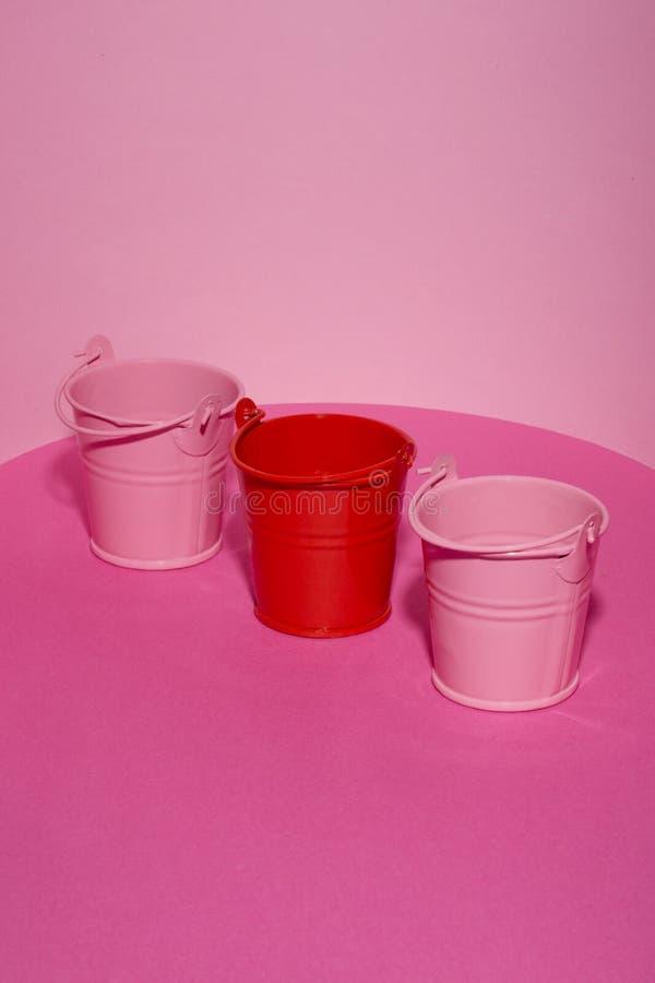 Drei Spielzeugeimer auf einem rosa Hintergrund lizenzfreie stockfotografie
