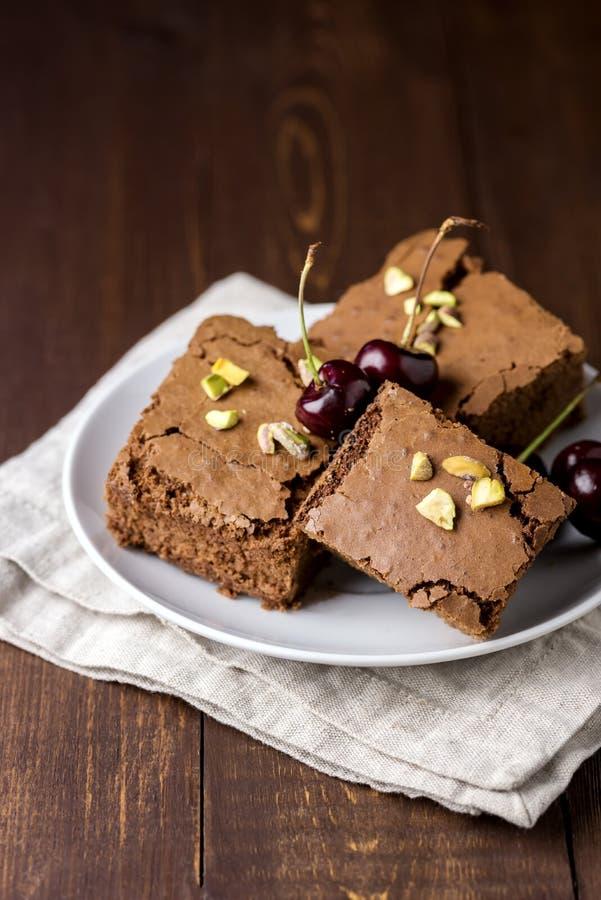 Drei Stücke geschmackvolle selbst gemachte Schokoladen-Schokoladenkuchen auf der weißen Platte verziert mit der Kirsche und Pista stockfotografie