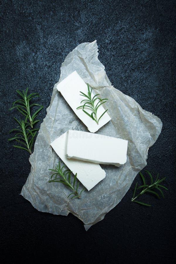 Drei Stücke organisches Feta auf dem Tisch, Rosmarinniederlassungen stockbilder