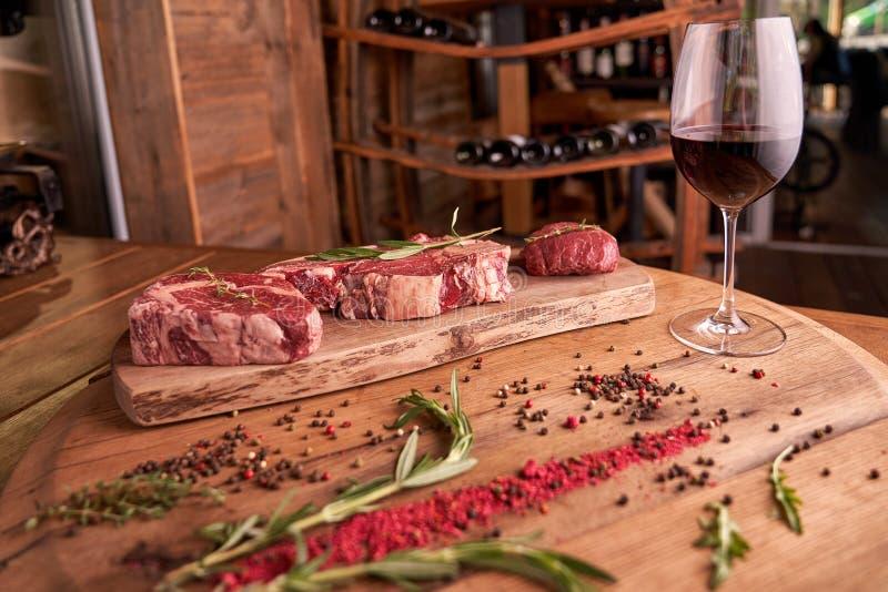 Drei Steaks Rippe ai auf einem hölzernen Schneidebrett mit einem Zweig des Rosmarins, der farbigen Pfefferkörner, der getrocknete lizenzfreies stockbild