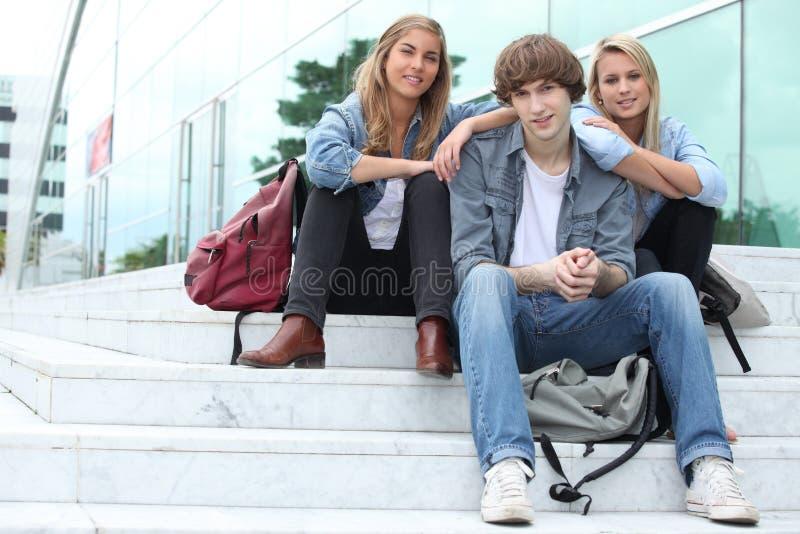 Drei Studenten, die draußen sitzen lizenzfreies stockfoto