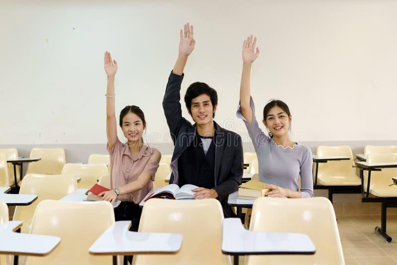 Drei Studenten hoben ihre Hände zusammen in das Klassenzimmer an lizenzfreies stockbild