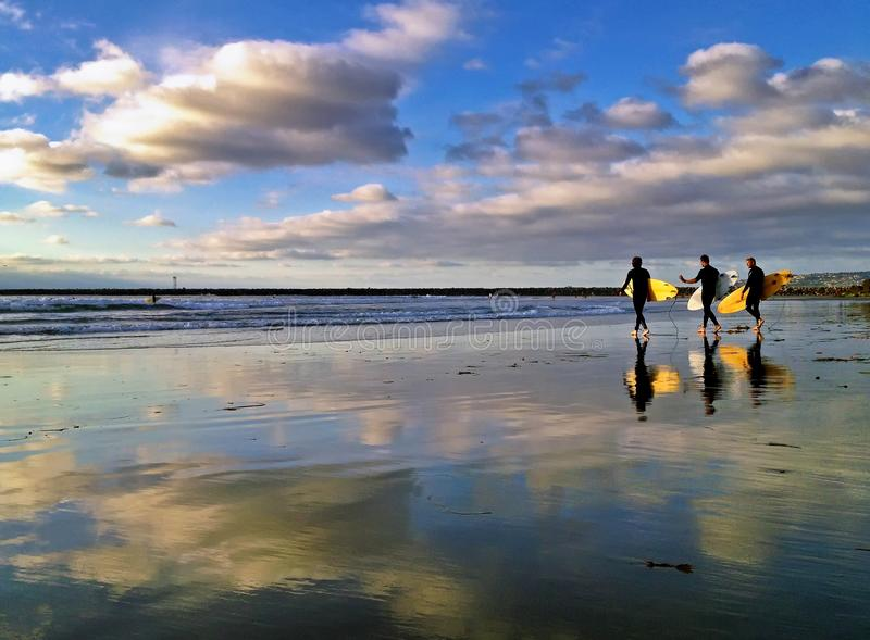 Drei Surfer gehen heraus zu den Wellen mit Reflexionen auf dem Strand voran lizenzfreie stockfotografie