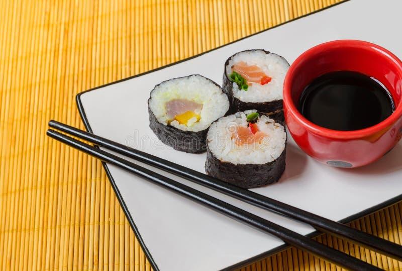 Drei Sushirollen mit Sojasoße und Essstäbchen stockbild