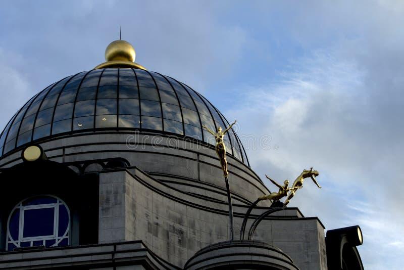 Drei synchronisierte Taucher von Rudy Weller am Kriteriums-Gebäude u. an seiner Glaskuppel im niedrigen Winkelsichtbild lizenzfreies stockbild