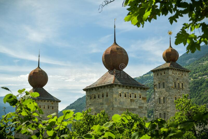 Drei Türme des Stockalper-Schlosses versteckt hinter den Bäumen in Brig, Schweiz stockbild
