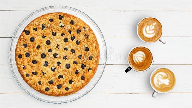 Drei Tasse Kaffees und selbst gemachter Kuchen verziert mit Mandeln und Blaubeeren auf weißem Holztisch lizenzfreies stockfoto