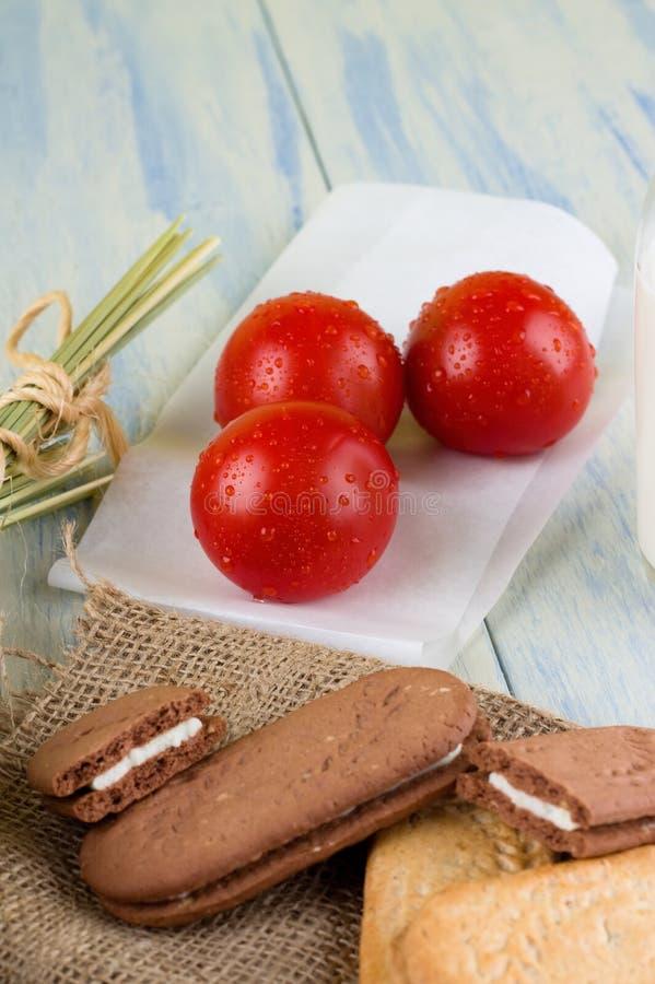 Drei taunasse Tomaten nahe bei Getreidekeksen stockfotos