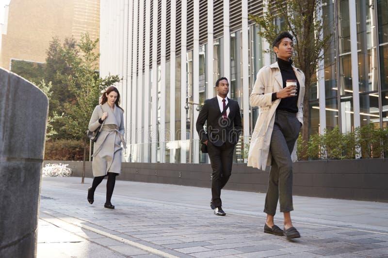 Drei tausendjährige Beamten, die in die Straße, niedriger Winkel, in voller Länge gehen stockfotos