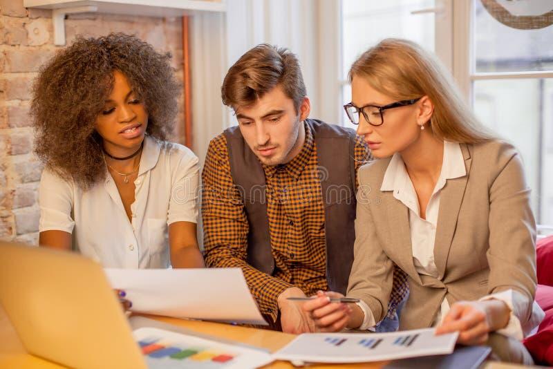 Drei Teilhaber, die graphigs und die Diskussion betrachten lizenzfreie stockfotos