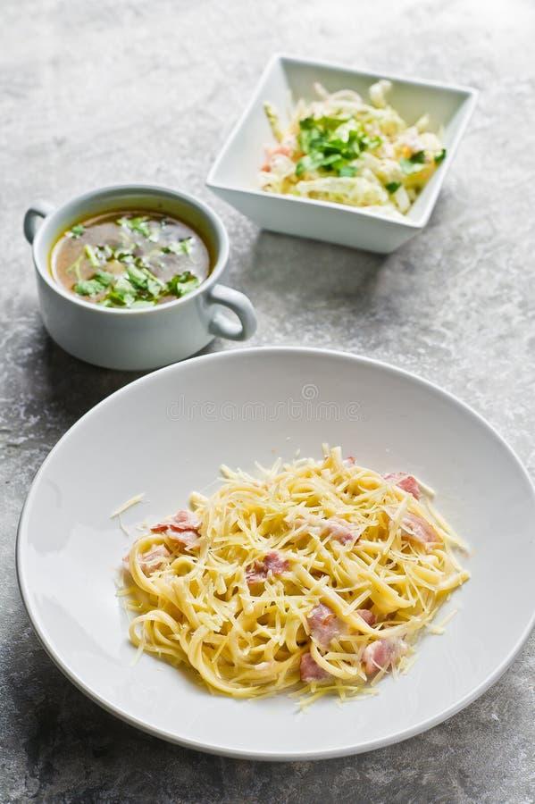 Drei Teller im Restaurant, in den Teigwaren Carbonara, im gr?nen Salat und in der H?hnersuppe stockbild