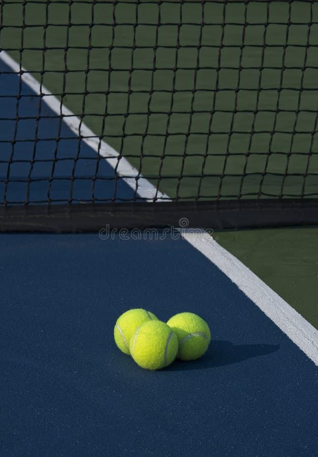 Drei Tennisbälle, die einen Morgen-Schatten werfen lizenzfreie stockbilder