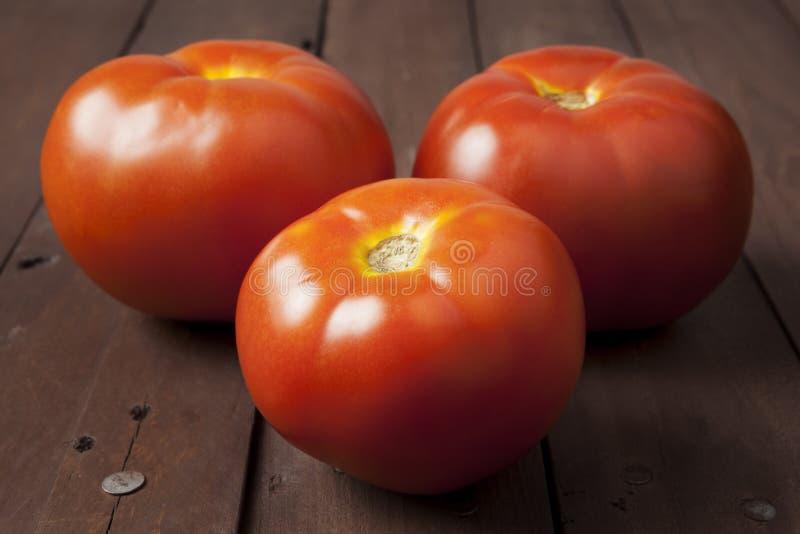 Drei Tomaten auf brauner Tabelle stockbild