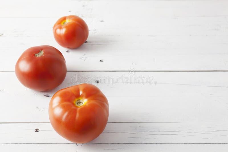 Drei Tomaten auf einer weißen Tabelle lizenzfreie stockfotos