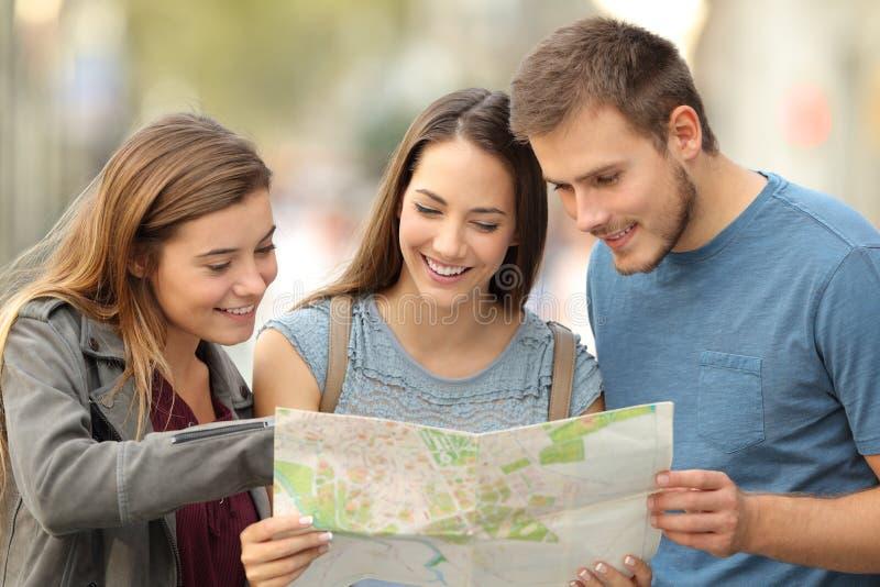 Drei Touristen, die eine Papierkarte auf der Straße konsultieren stockbilder
