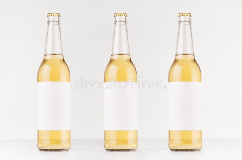 Drei transparente longneck Bierflaschen 500ml mit leerem weißem Aufkleber auf weißem hölzernem Brett, verspotten oben lizenzfreie stockbilder