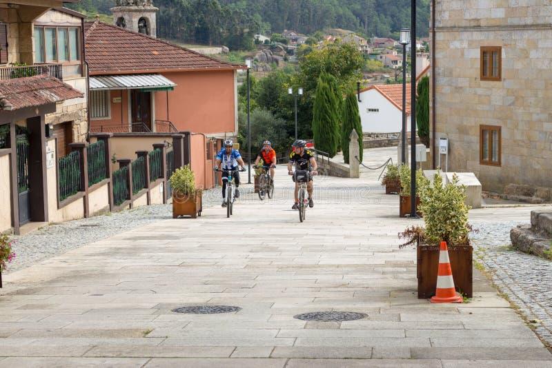 Drei unbekannte Radfahrer, die herauf den Hügel in der alten Stadt, Spanien reiten Drei Freunde auf Fahrrädern an der Straße in E stockfotografie