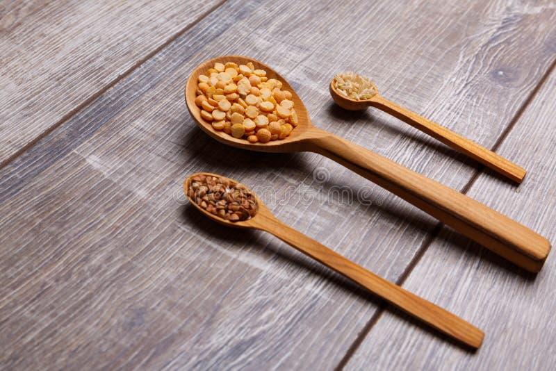 Drei verschiedene hölzerne Löffel mit Getreide auf dem Tisch stockbilder